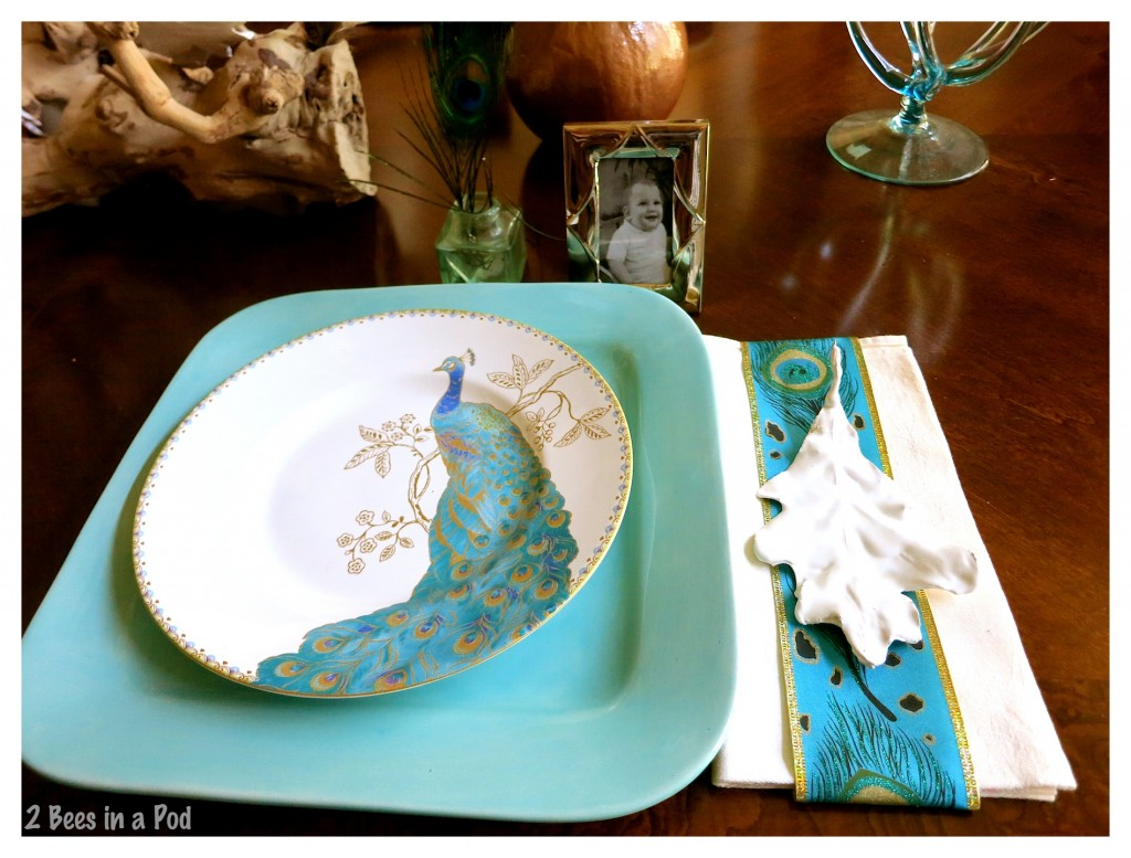 Turquoise and copper Fall tablescape. Each place setting has a vintage inkwell, vintage framed photo, peacock feathers and a white plaster leaf
