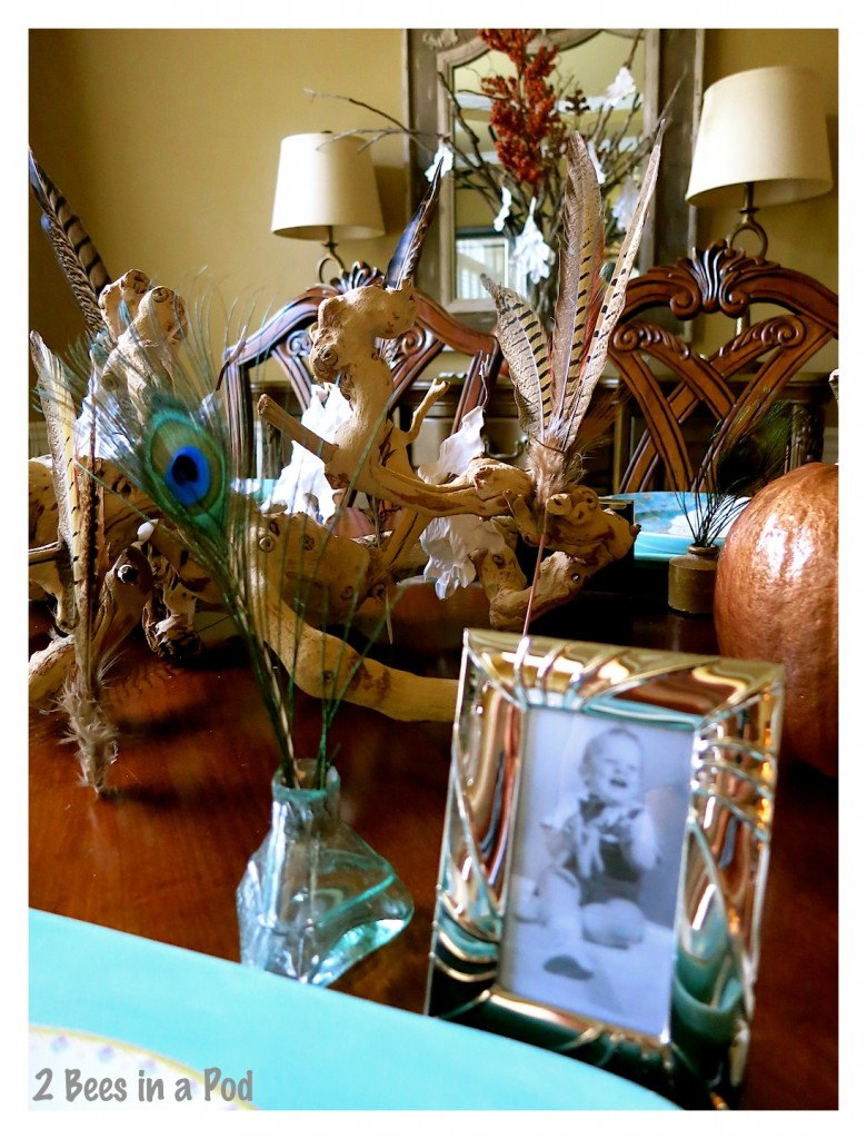 Vintage inkwells and framed vintage photographs compliment each place setting. The use of turquoise and copper brighten the dining room with this Fall tablescape. The peacock feathers add a touch of whimsy