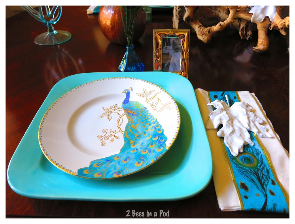 Fall tablescape using bright turquoise, peacock china, peacock feathers, vintage inkwells, framed vintage photos and white plaster leaves