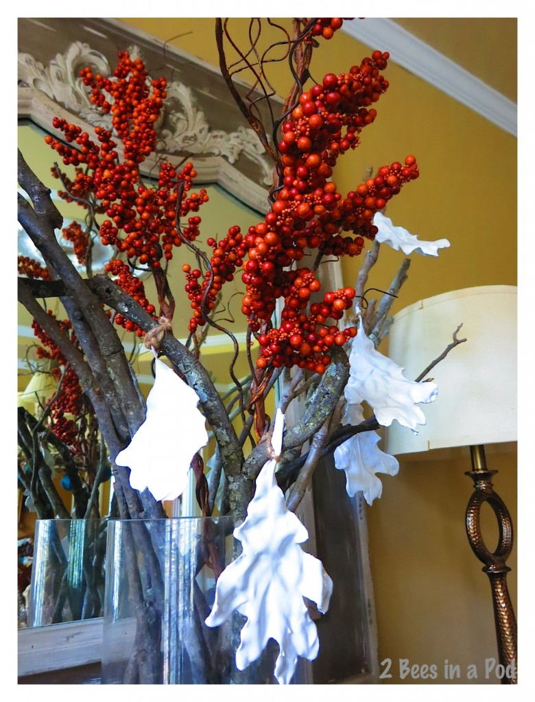 Copper pick berries, white plaster leaves and collected branches sit atop the dining room sideboard as a compliment to the Fall tablescape.
