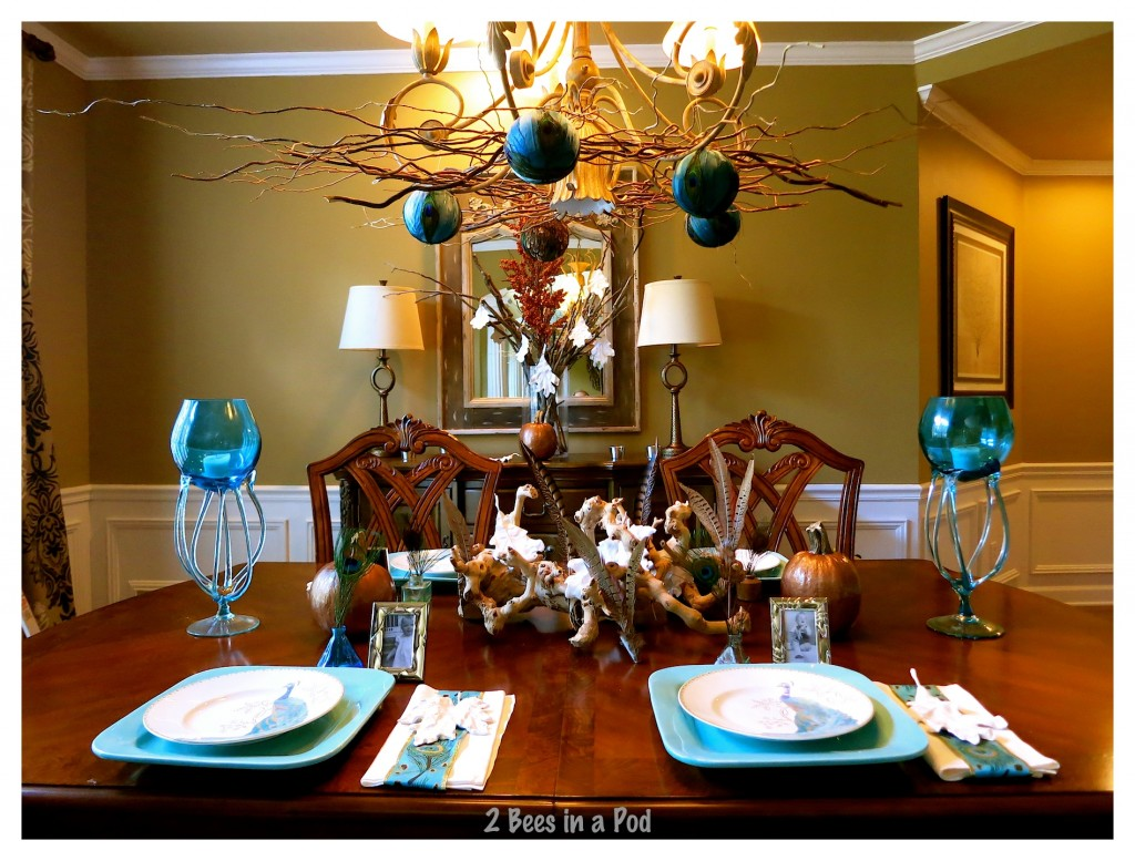 Turquoise and copper Fall tablescape. Vintage elements adorn the table. Curly willow branches and peacock ornaments decorate the chandelier.