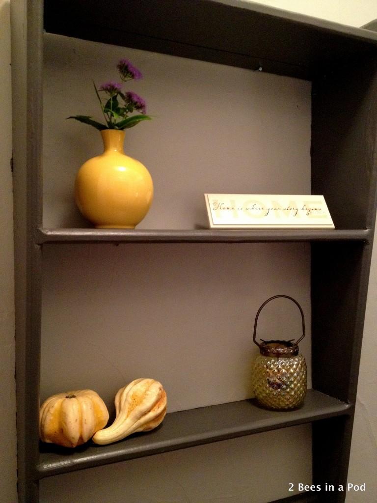 Dark grey shelves with yellow vase, lantern, & gourds