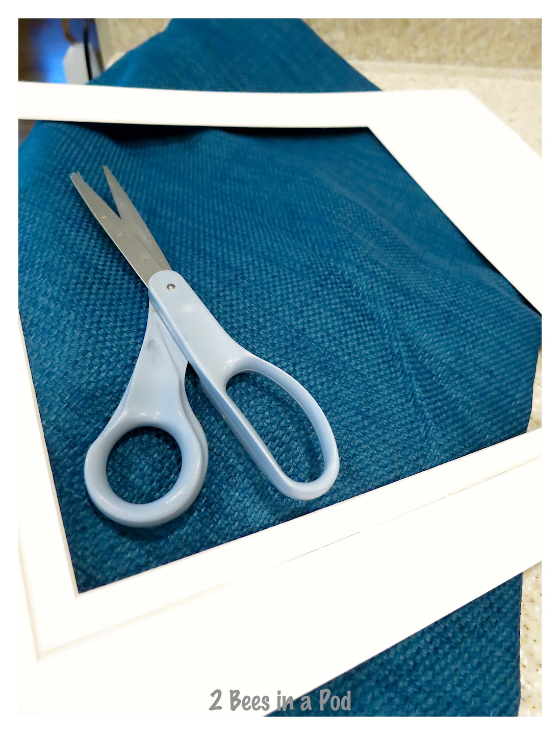 Cutting the fabric to use for the pocket board - total project took 15 minutes! Repurposed a garage sale frame.