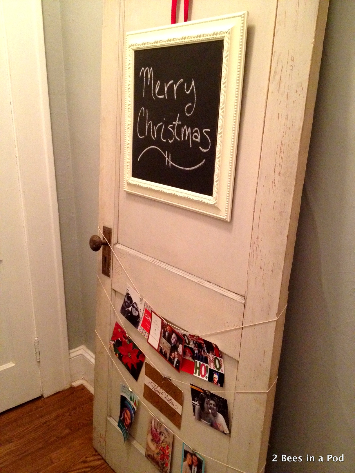 Christmas card holder with chalkboard with ribbon and twine to hold cards.