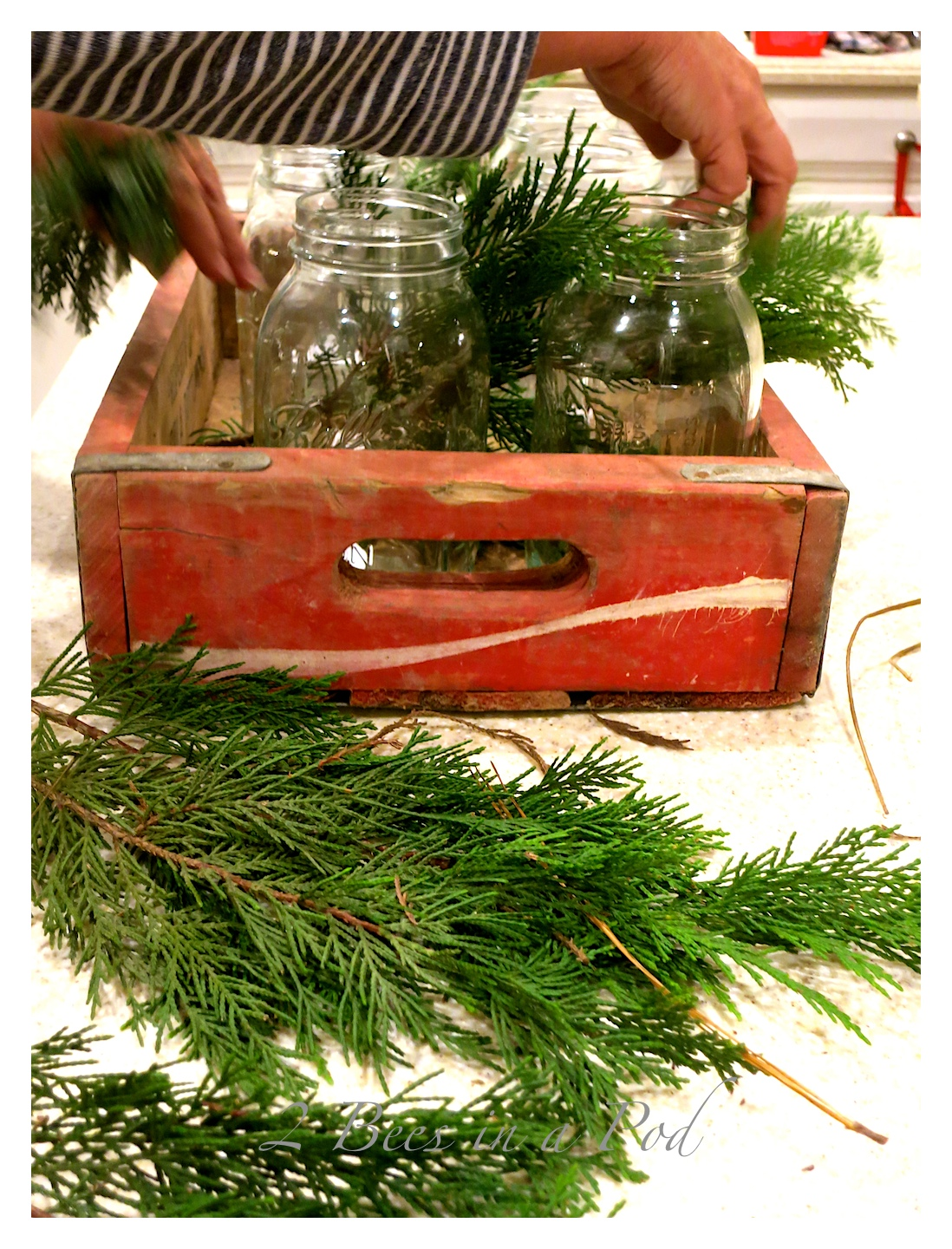 I used a vintage Coke crate as Christmas centerpiece by adding Mason jars, tea lights, evergreen, pinecones and berries