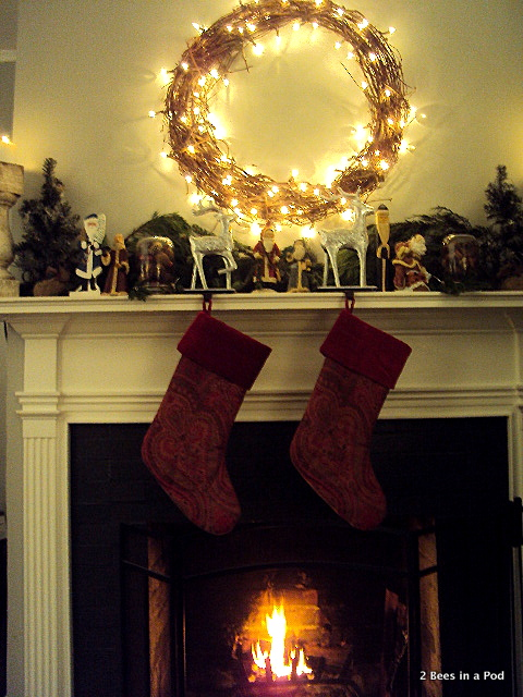 Stockings from Pottery Barn, hand painted Santa's, greenery, burlap, grape vine wreath, lit fireplace, Christmas Mantle
