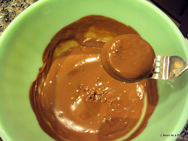Dipping Ritz Cracker Peanut Butter sandwich into chocolate