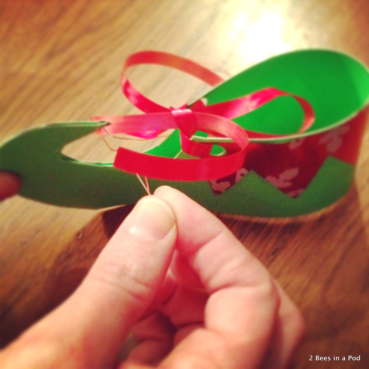 Using a needle to thread bell onto elf feet