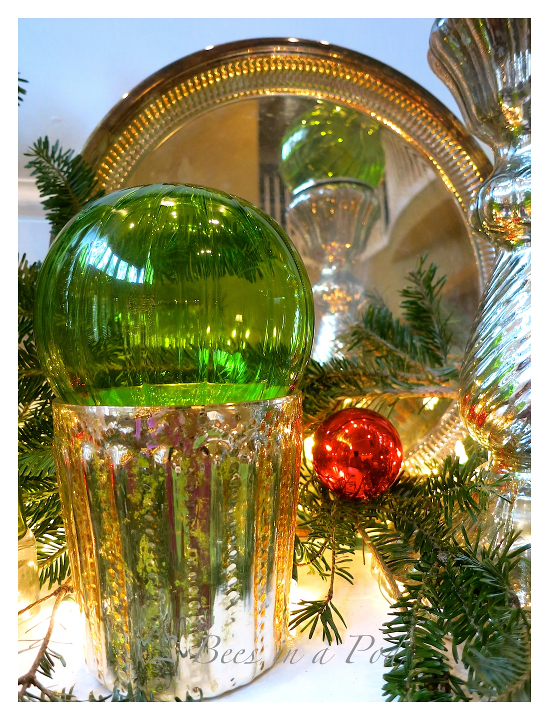 Traditional Christmas mantle decor using Mercury glass, green and red. I also used vintage silver trays as a backdrop.
