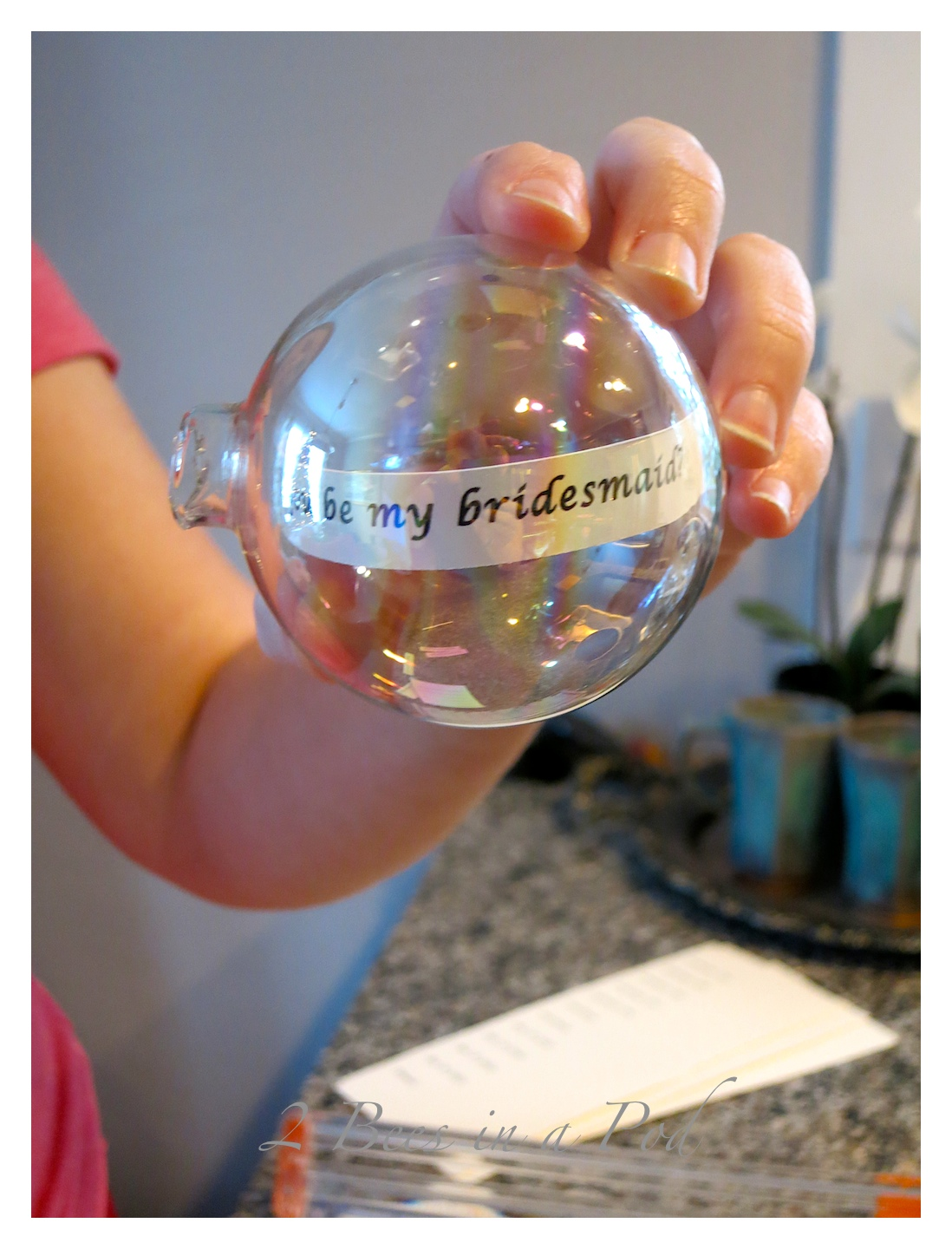 """Putting strips of paper into the """"Will you be my Bridesmaid"""" ornament"""