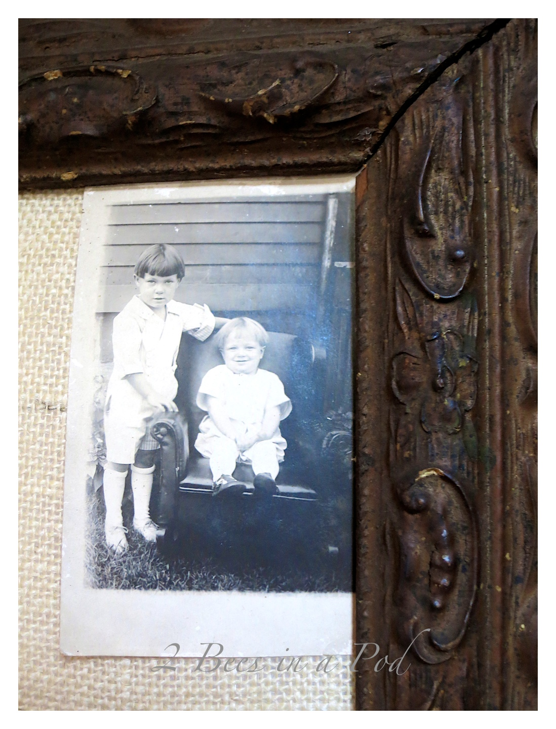 DIY burlap bulletin board. Made from a salvaged antique frame, burlap, foam board and batting. Cute decorated with vintage decor.Ancestors from long ago...love the vintage photos