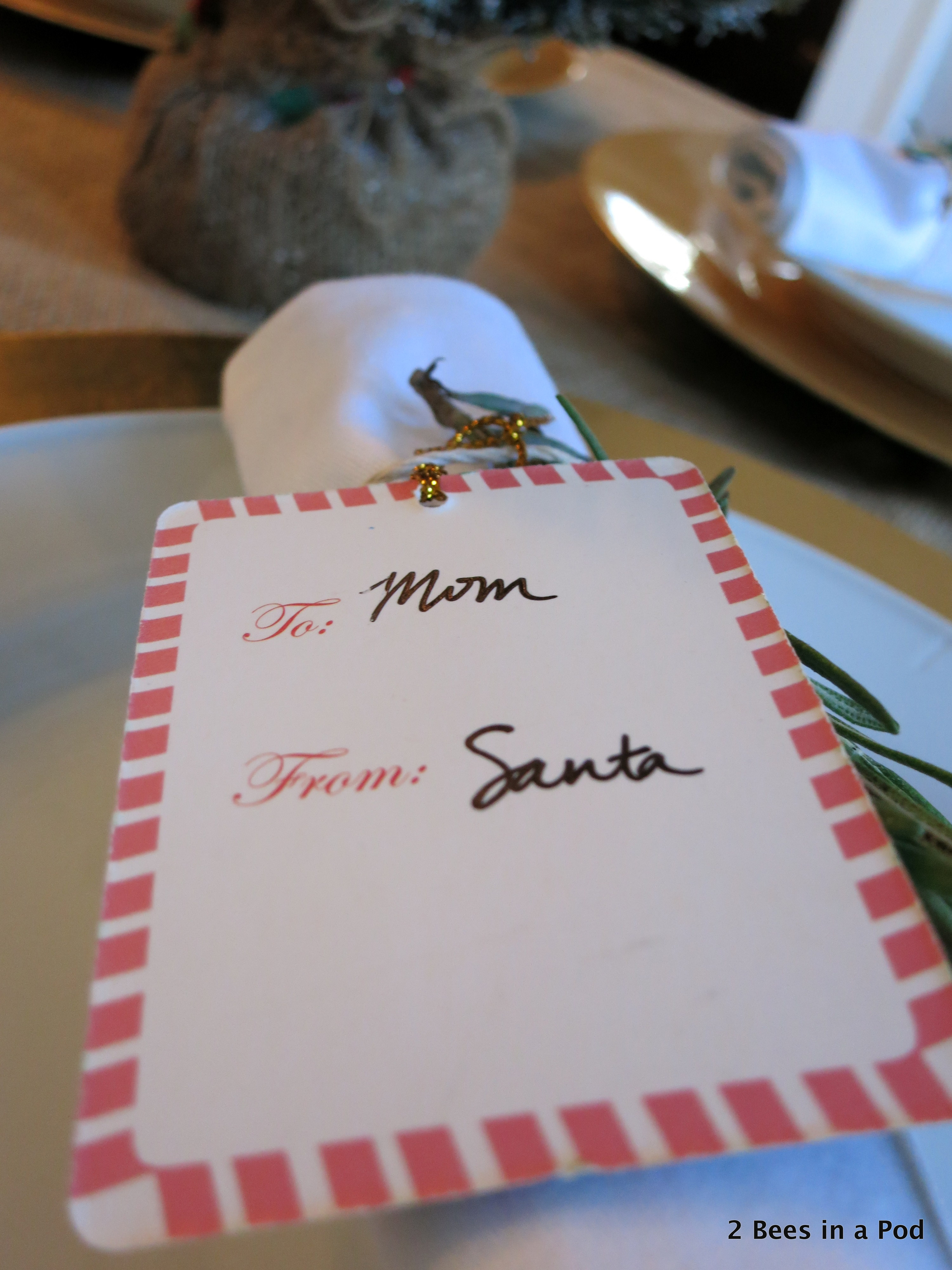 Christmas Home Tour. Dining Room Tablescape with burlap tablecloth and rosemary sprig with santa gift tag around white napkin 3