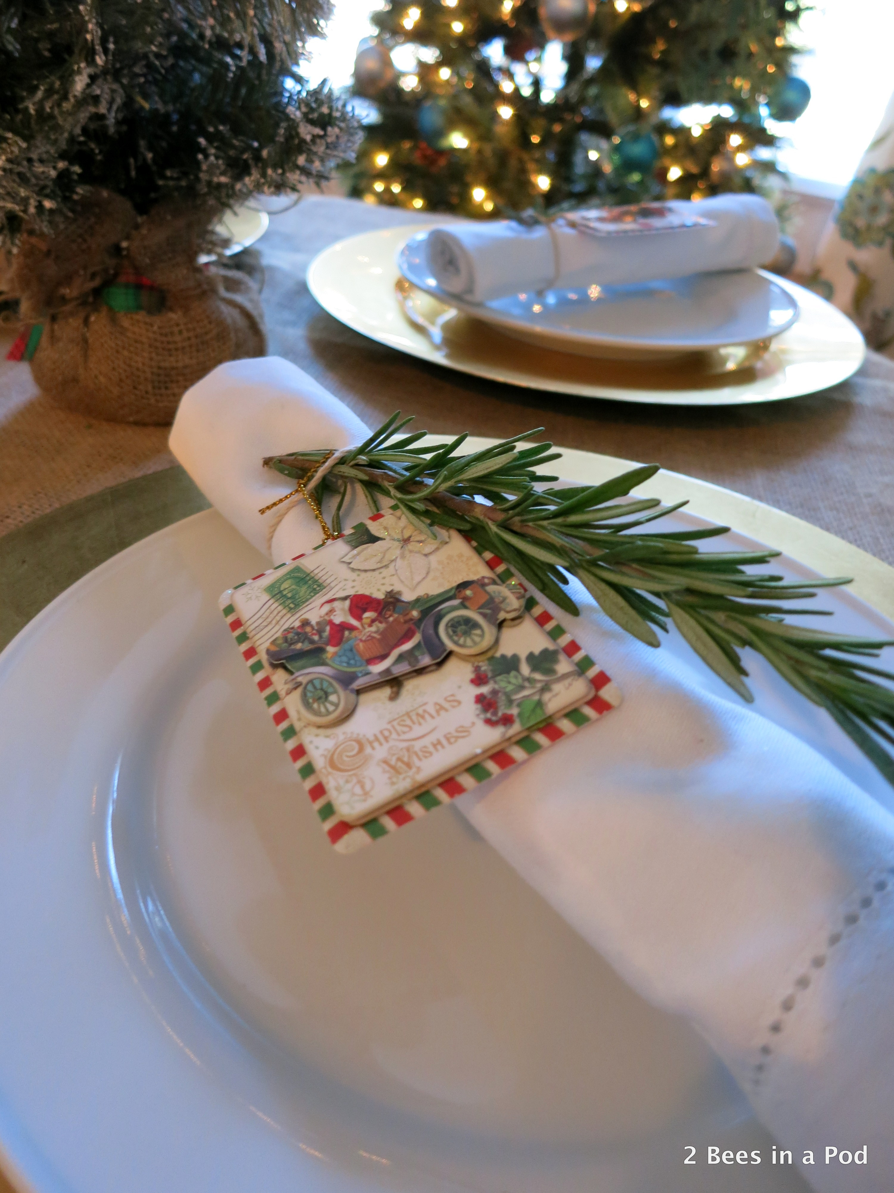 Christmas Home Tour. Dining Room Tablescape with burlap tablecloth and rosemary sprig with santa gift tag around white napkin 4
