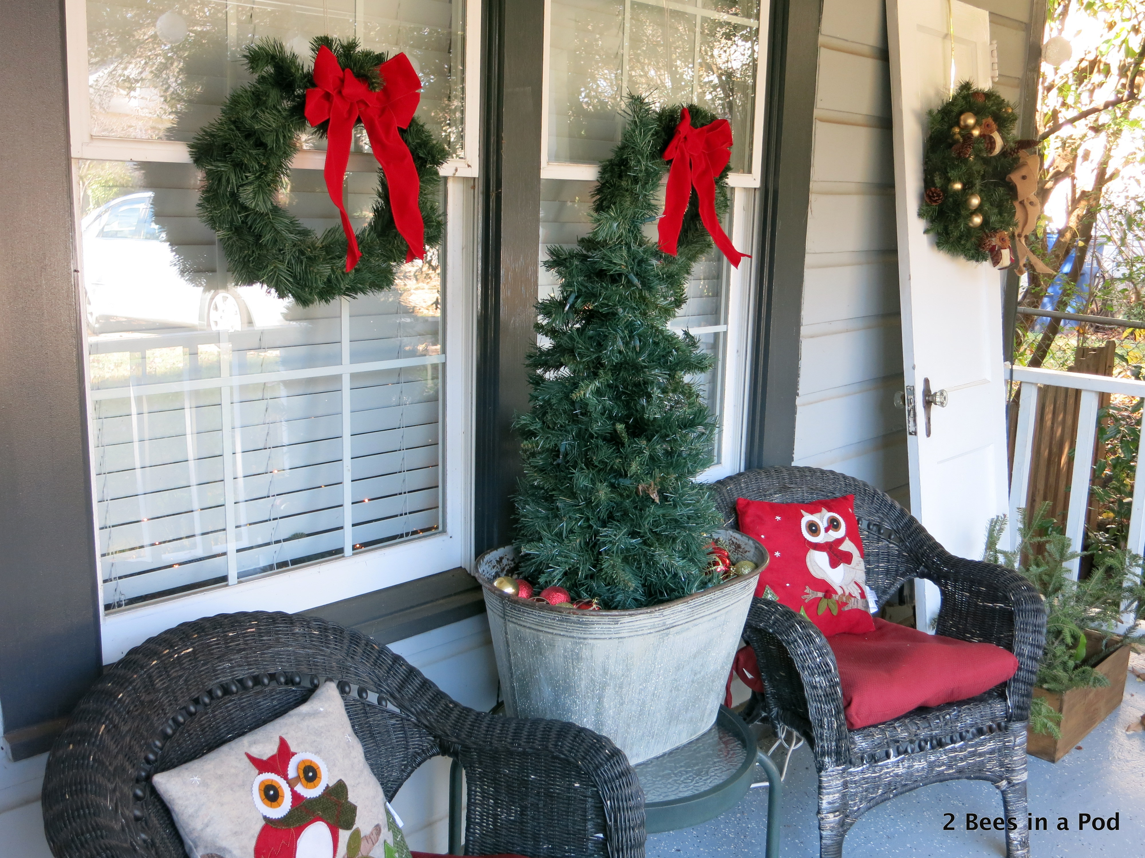 Christmas Home Tour. Exterior Front Porch with owl pillows, tree in galvanized bucket and wreaths