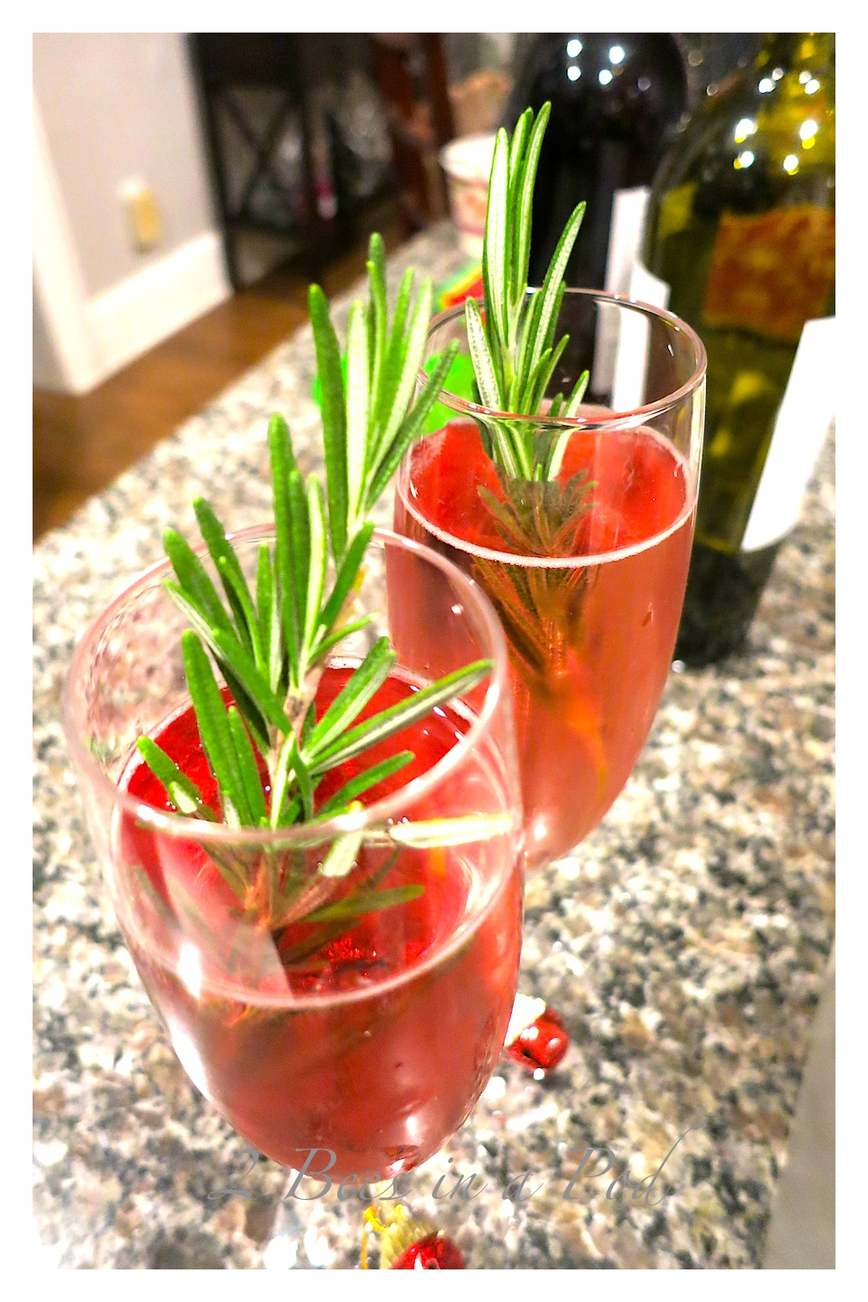 Poinsettia Cocktail - festive for parties. Persecco, cranberry juice and fresh rosemary garnish. Love the added red jingle bells on the champagne flutes.