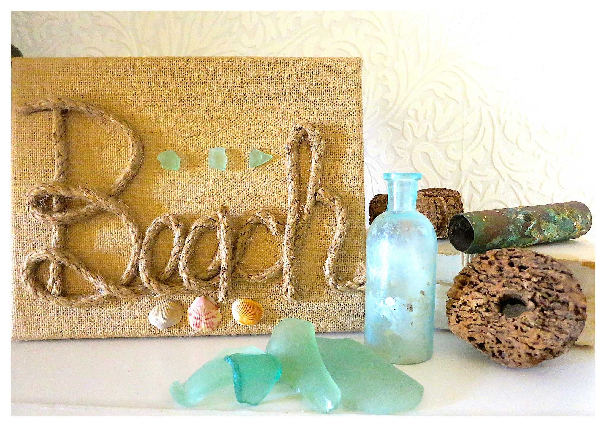 "DIY Burlap Canvas Beach Art. Super simple artwork - add jute or rope to spell out ""Beach"" and embellish with shells and sea glass!"