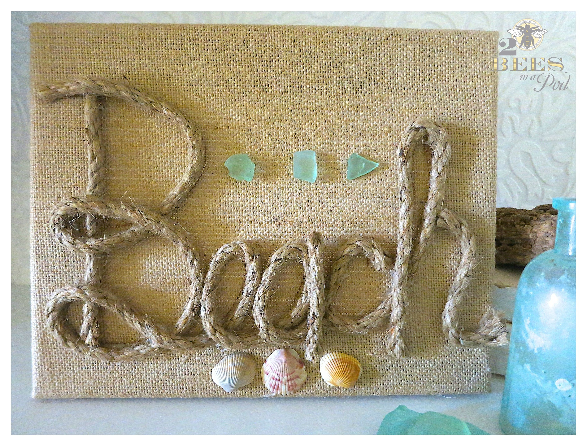 """DIY Burlap Canvas Beach Art. Super simple artwork - add jute or rope to spell out """"Beach"""" and embellish with shells and sea glass!"""