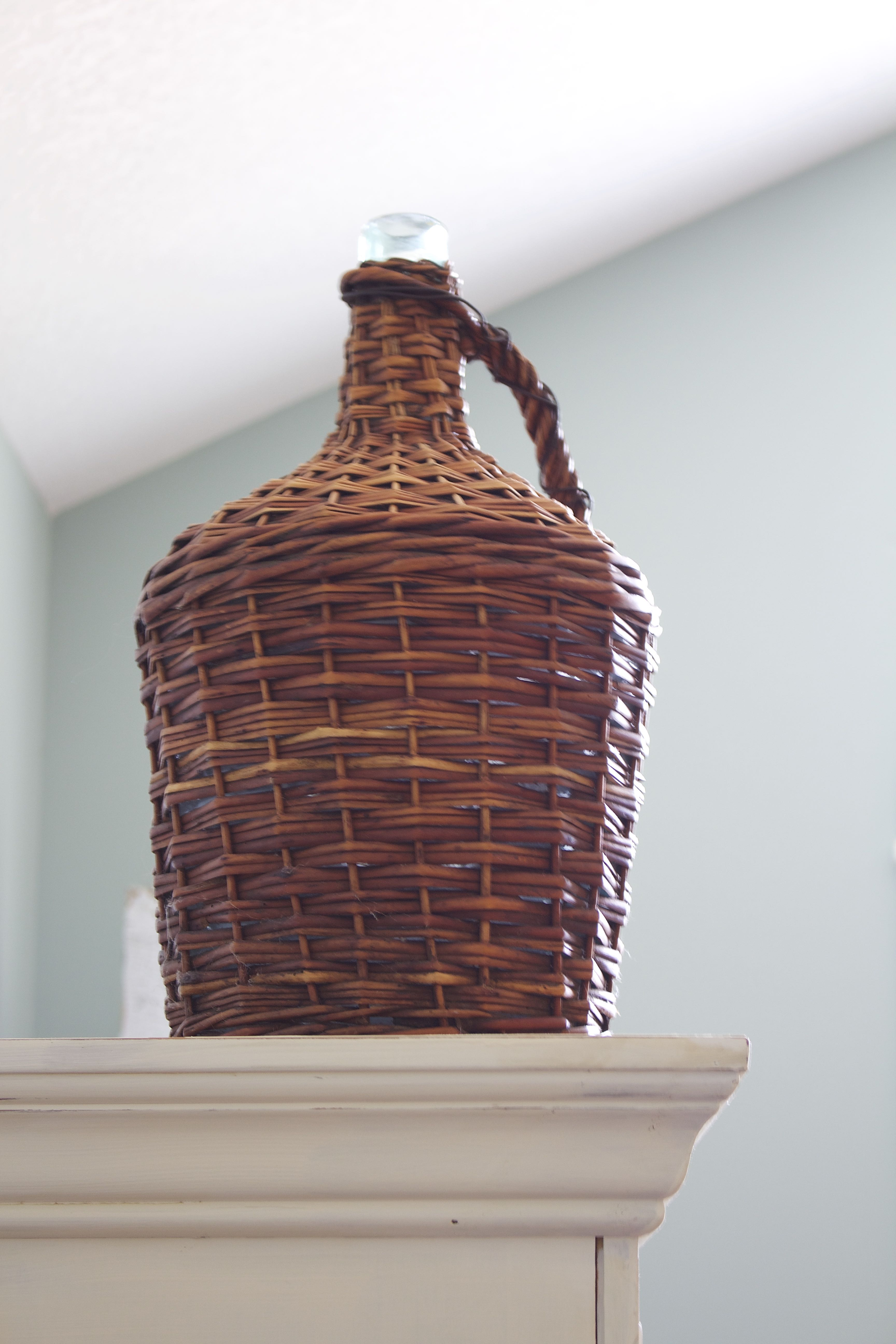 Added height on the painted armoire with a vintage wicker wine basket. Chalk painted armoire transformation.