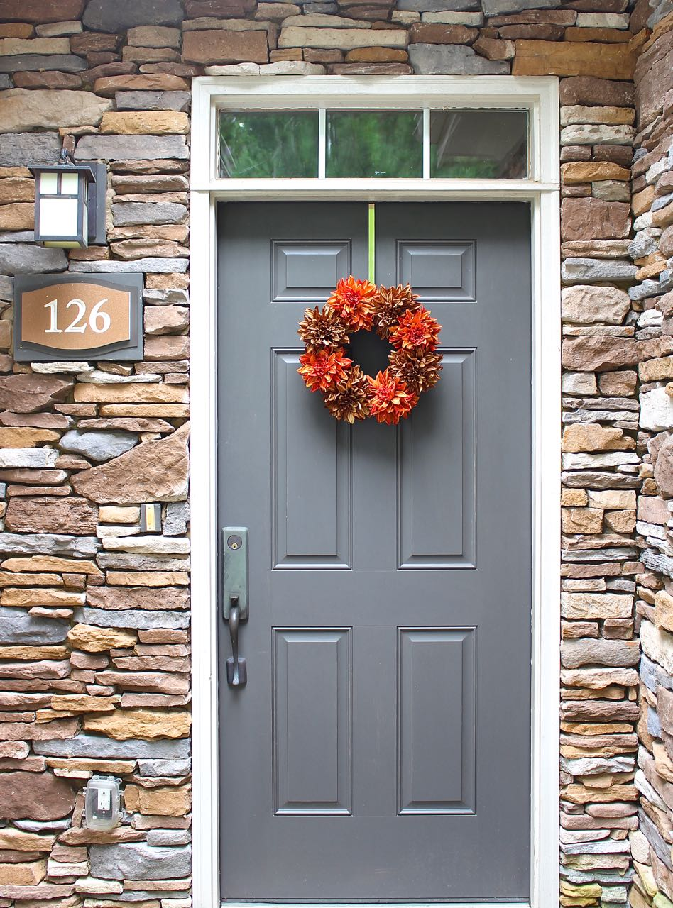 The stack stone and gray door really make the orange floral stems pop. Such an easy and cute craft.