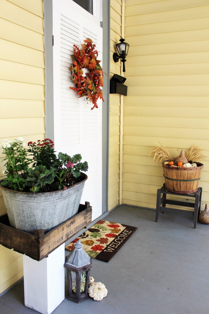 Fall entryway with white pumpkins, wheat, kale, mums, & rustic lantern and apple basket