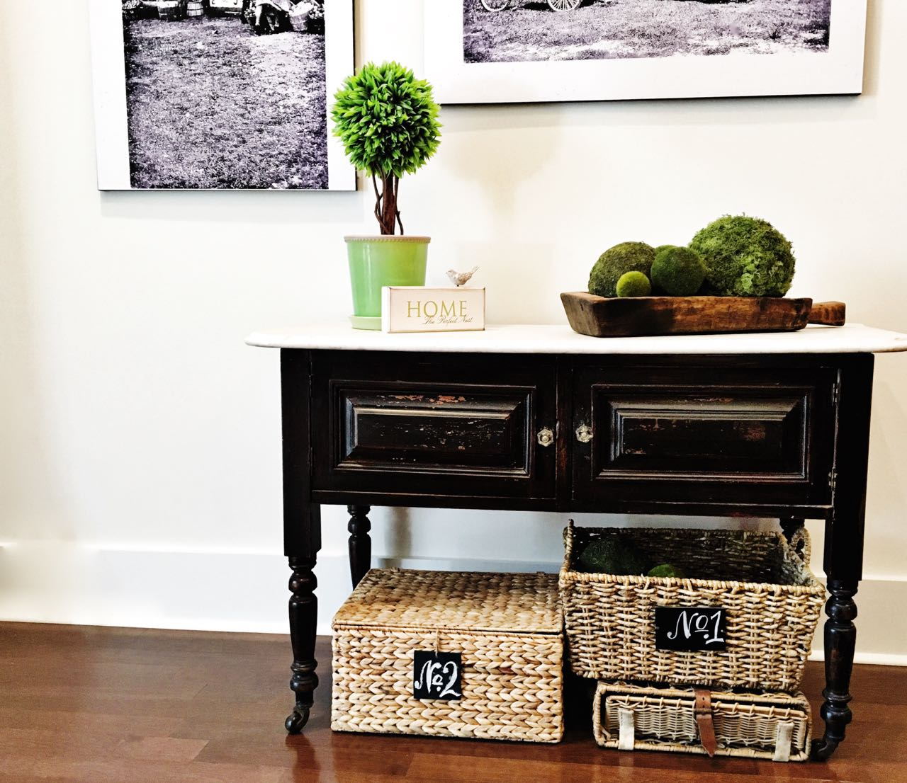 This vintage antque table looks beautiful underneath the engineer print wall decor. The baskets with chalkboards add texture.