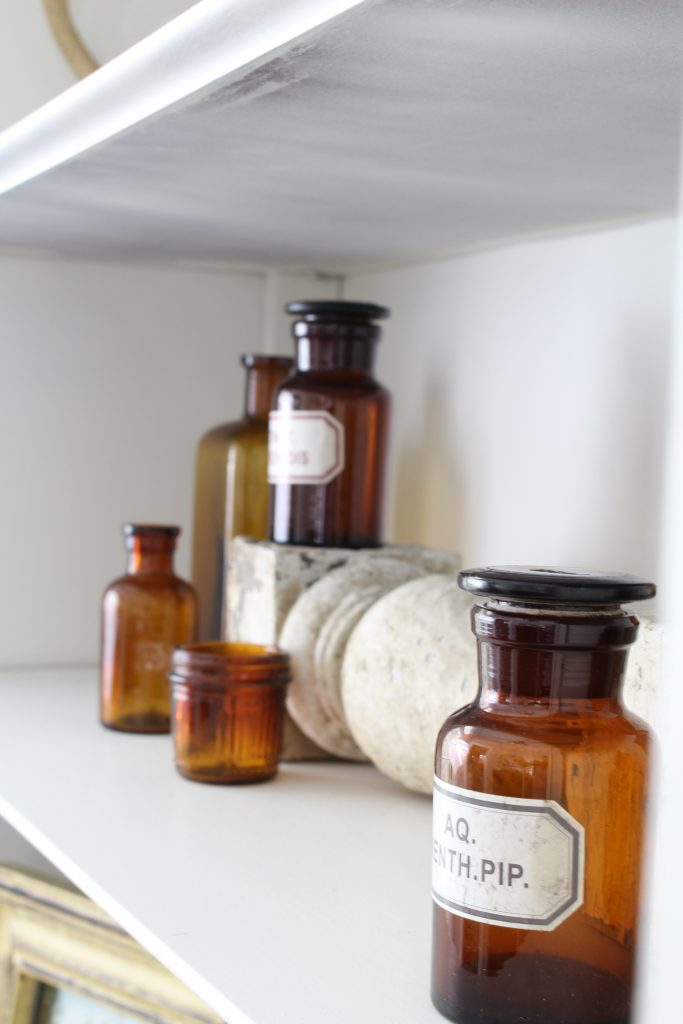Fall home tour. Entryway shelves decorated with vintage glass bottles.