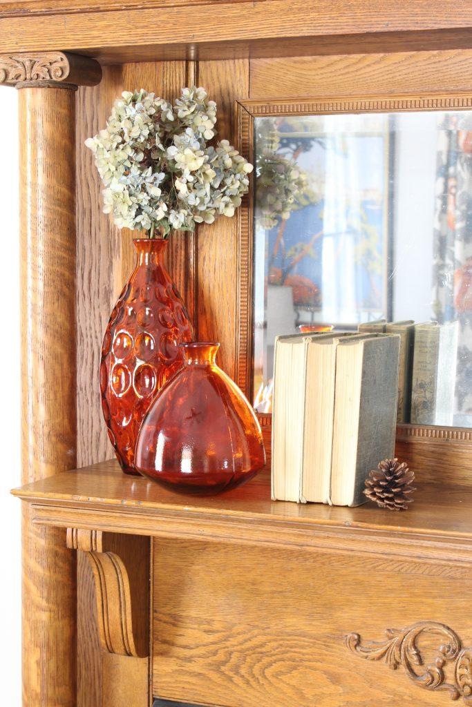 Fall mantel decor with orange glass bottles. Fall home decor.