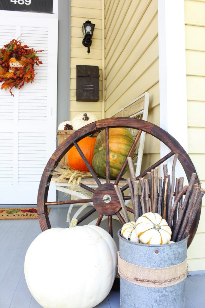 Rustic wagon wheel and white pumpkins for Fall front porch.s
