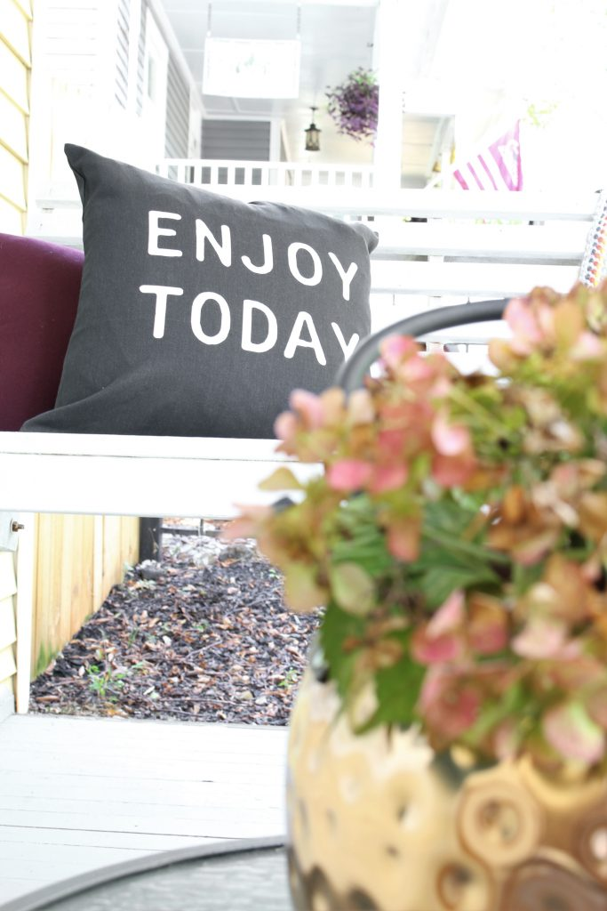 Fall front porch with enjoy today pillow.