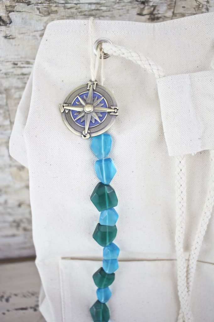 DIY Beach Bag Backpack. Add the sea glass beads and compass charm to the canvas bag.