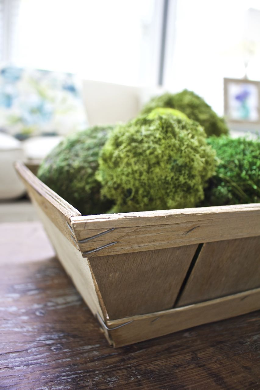 DIY Aged Market Basket. Now the basket looks vintage and beautiful with moss green balls.