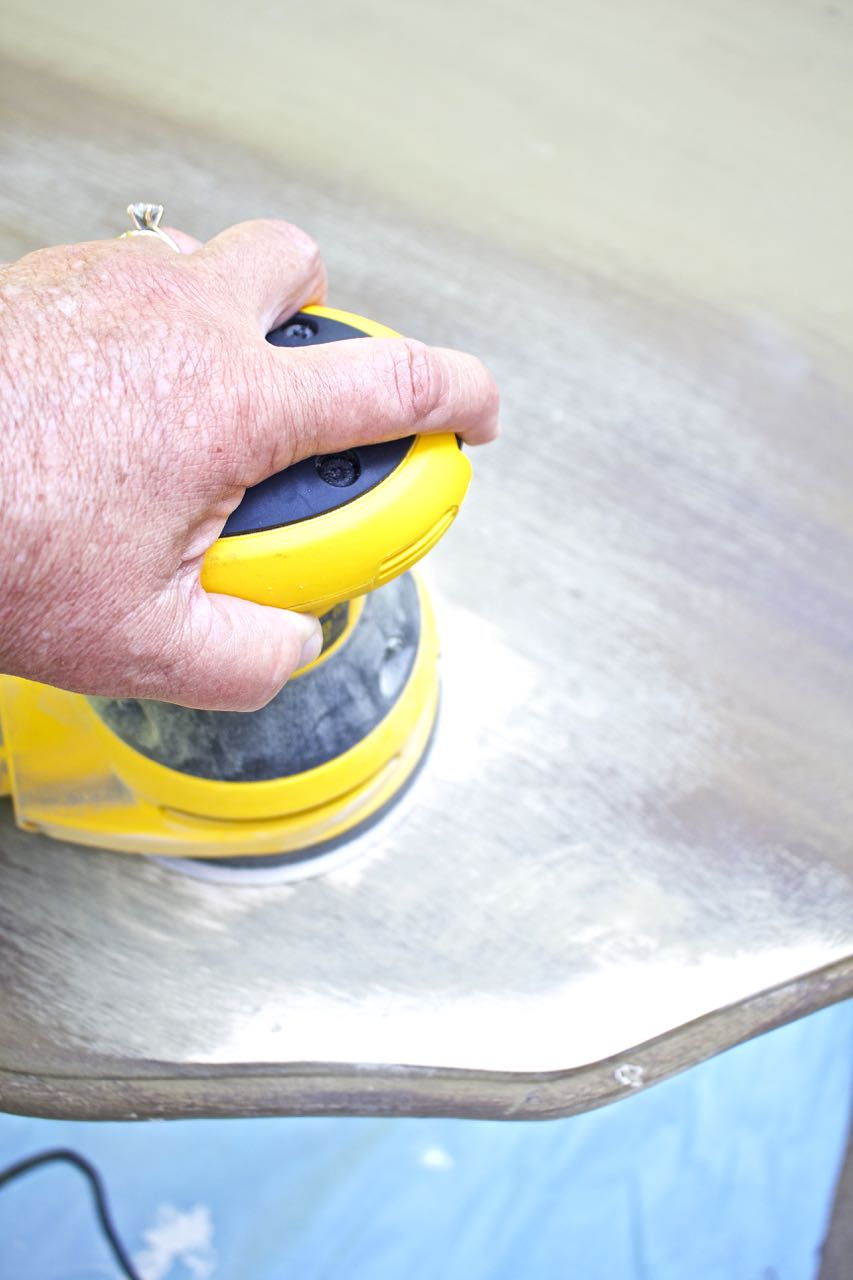 Dining Room Table Makeover. Use a palm sander to remove layers of paint from table.