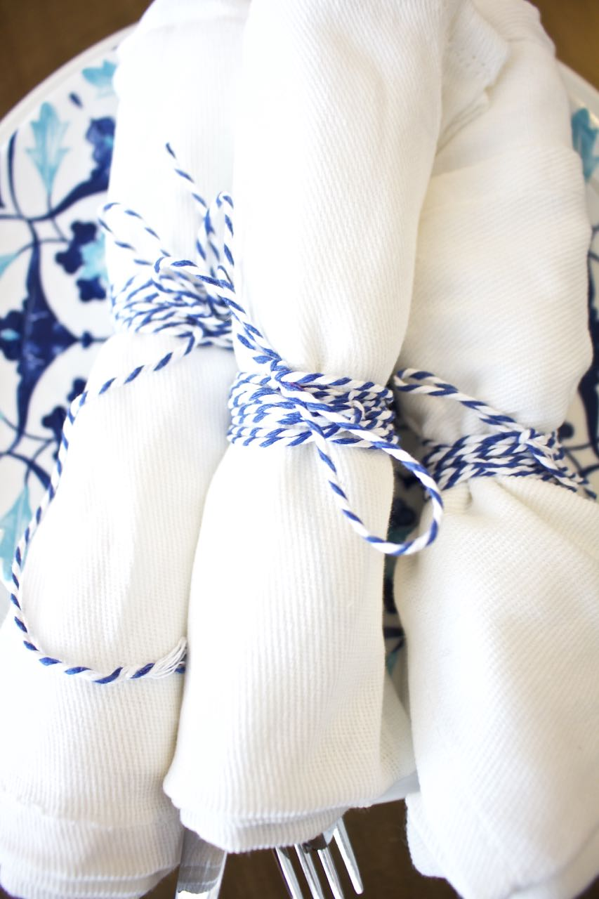 Shades of Blue Summer Tablescape. When entertaining wrap silverware in a white cloth napkin and tie with blue and white bakers twine.