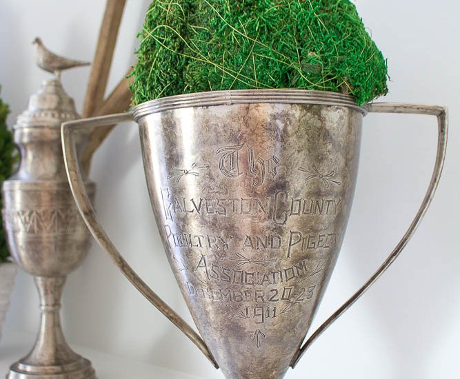 Hello Spring Mantel. Two vintage trophies with green moss ball for spring mantel.